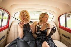 Femme deux de fantaisie s'asseyant dans la rétro voiture et appréciant la vie Photos stock