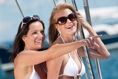 Femme deux de sourire attirante sur le bateau à voiles photo libre de droits