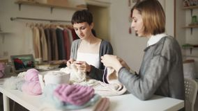 Femme deux de tricotage travaillant dans l'atelier de textile Mains de tricotage de passe-temps de femme banque de vidéos