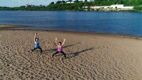 Femme deux faisant le yoga sur la plage de sable par la rivière dans la ville Belle vue de ville dans le lever de soleil banque de vidéos