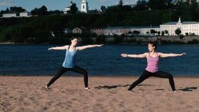 Femme deux faisant le yoga sur la plage de sable par la rivière dans la ville Belle vue de ville dans le lever de soleil Pose de  clips vidéos