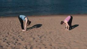 Femme deux faisant le yoga sur la plage par la rivière dans la ville Belle vue banque de vidéos