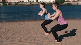 Femme deux faisant le yoga sur la plage par la rivière dans la ville Belle vue Pose d'Utkatasana banque de vidéos