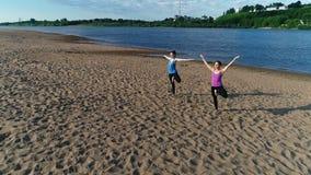 Femme deux faisant le yoga sur la plage par la rivière dans la ville Belle vue Pose de Vrikshasana clips vidéos