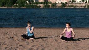 Femme deux faisant le yoga sur la plage par la rivière dans la ville et parler Belle vue banque de vidéos