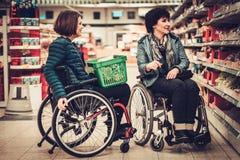 Femme deux handicapée dans fauteuils roulants dans une épicerie Images libres de droits