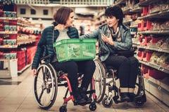 Femme deux handicapée dans fauteuils roulants dans une épicerie Images stock
