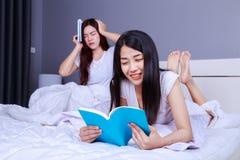 Femme deux lisant un livre sur le lit dans la chambre à coucher Image libre de droits