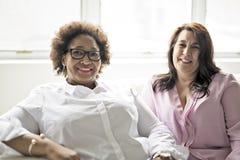 Femme deux mûre s'asseyant sur le sofa à la maison photographie stock