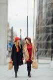 Femme deux occupée marchant sur la rue, parlant les uns avec les autres Image libre de droits