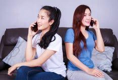 Femme deux parlant au téléphone portable sur le sofa dans le salon à la maison Photos stock