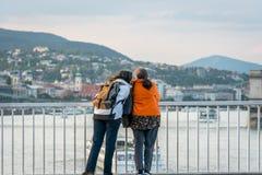 Femme deux parlant et se penchant contre une balustrade en acier sur un pont à Budapest Hongrie Photos libres de droits