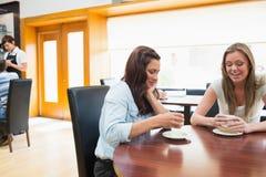 Femme deux s'asseyant en cafétéria et café potable Photo stock