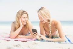 Femme deux se trouvant sur la plage et regardant le téléphone portable Photos stock