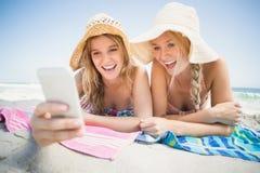 Femme deux se trouvant sur la plage et regardant le téléphone portable Image stock