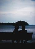 Femme deux sous le parapluie en mer Photo stock