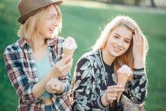 Femme deux tenant le cône de fonte de gaufre de crème glacée dans des mains sur la lumière d'été Photographie stock