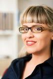 Femme devant l'étagère de livre Image libre de droits