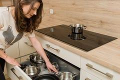 Femme devant le cuiseur moderne avec le tiroir ouvert sous le fourneau Photos libres de droits