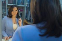 Femme devant un miroir dans le vestiaire images libres de droits
