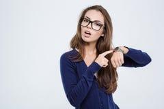 Femme dirigeant le doigt sur la montre-bracelet Photos stock