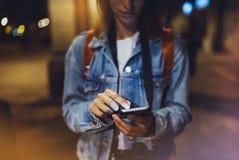 Femme dirigeant le doigt sur le smartphone d'écran vide sur la lumière de bokeh de fond dans la ville atmosphérique de nuit, util photo libre de droits