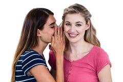 Femme disant le secret à l'ami Photographie stock