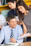 Femme discutant avec le professeur While Classmates In photo stock