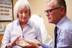 Femme discutant l'augmentation de sein avec le chirurgien plasticien images stock