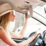 Femme distraite conduisant sa voiture regardant dans le miroir images stock