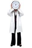 Femme docteur retenant l'horloge avant son visage Images stock
