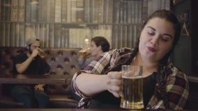Femme dodue avec des tresses se reposant au compteur de barre avec un verre de bière tandis que deux hommes parlant avec enthousi banque de vidéos