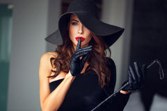Femme dominante sexy dans le chapeau et le fouet ne montrant aucun entretien Photographie stock libre de droits