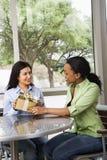 Femme donnant à ami féminin un cadeau Photo stock