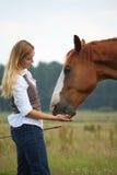 Femme donnant à cheval un festin Photographie stock libre de droits