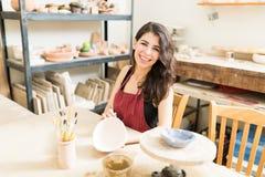 Femme donnant des contacts de finale à Clay Bowl In Pottery Studio photo stock
