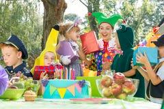 Femme donnant des présents aux enfants Image stock