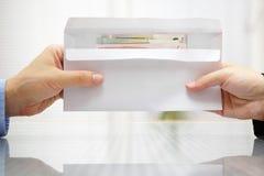 Femme donnant l'enveloppe avec l'argent à l'homme Photographie stock libre de droits