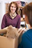 Femme donnant les articles non désirés à la boutique de charité Photographie stock