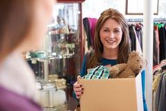 Femme donnant les articles non désirés à la boutique de charité Images stock