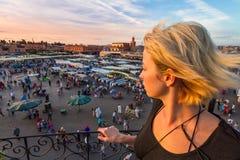 Femme donnant sur la place du marché d'EL Fna de Jamaa dans le coucher du soleil, Marrakech, Maroc, Afrique du Nord Photographie stock libre de droits