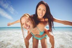 Femme donnant sur le dos à son ami féminin Images libres de droits