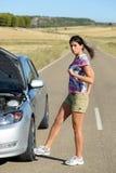 Femme donnant un coup de pied la roue de voiture cassée de moteur Image stock