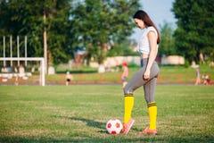 Femme donnant un coup de pied le ballon de football photographie stock libre de droits