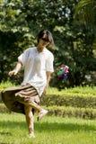 Femme donnant un coup de pied le shuttlecock sur la pelouse Photo libre de droits