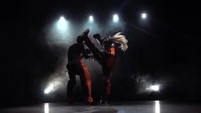 Femme donnant un coup de pied le type ils sont boxe d'entraînement pour kickboxing Fumez le fond Mouvement lent Lumière par derri banque de vidéos