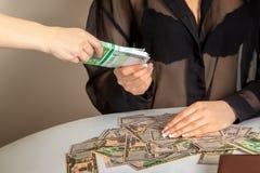 Femme donnant un paiement illicite à un paquet d'euro argent Photos stock