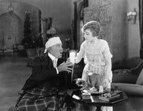 Femme donnant un verre de breuvage magique à un homme de malade (toutes les personnes représentées ne sont pas plus long vivantes Image stock