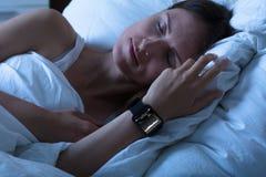 Femme dormant avec la montre intelligente montrant le taux de battement de coeur images stock