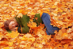 Femme dormant dans des feuilles d'automne photos stock
